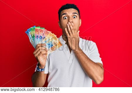 Young arab man holding swiss franc banknotes covering mouth with hand, shocked and afraid for mistake. surprised expression