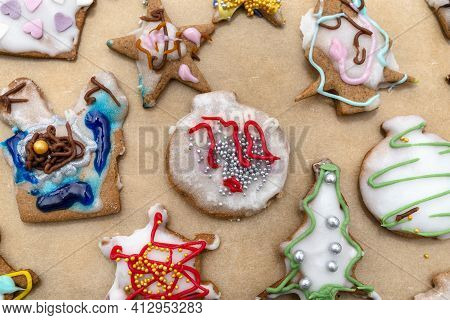 Hand Decorated Baked Gingerbreads Of Various Shapes, Arranged On Baking Paper, Top View.