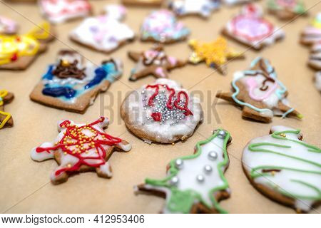 Hand Decorated Baked Gingerbreads Of Various Shapes, Arranged On Baking Paper.