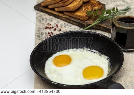 Fried Eggs In A Rustic Iron Pan, Toast On A Wooden Board And A Cup Of Coffee For Breakfast.