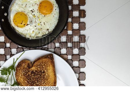 Fried Eggs In A Rustic Iron Pan, Toast On A Dish For Breakfast. Copy Space. Top View