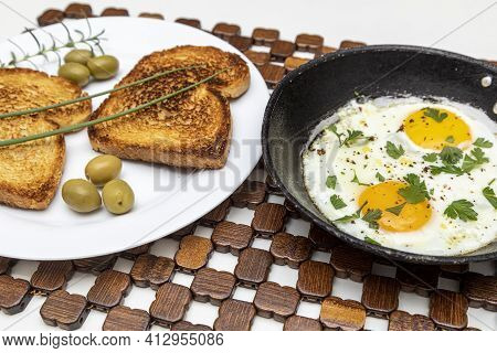 Fried Eggs In A Rustic Iron Pan, Toast On A Dish For Breakfast