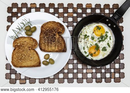 Fried Eggs In A Rustic Iron Pan, Toast On A Dish For Breakfast. Top View