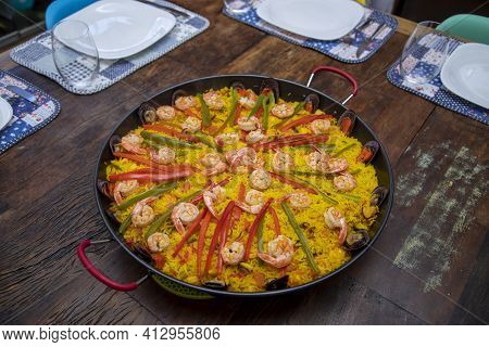 Traditional Seafood Paella In The Fry Pan On A Wooden Old Table
