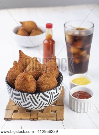 Typical Brazilian Snack Coxinha On A Plate With Soda Glass, Ketchup, Pepper And Mustard.