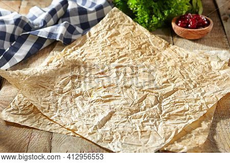 Baking paper with food ingredients. Wooden table at kitchen with baking utensil and fresh vegetables. Crumpled parchment or baking paper as a creative copy space