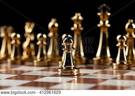 Golden Chess Figures Standing On Wooden Chessboard. Intellectual Duel And Tactical Battle In Busines