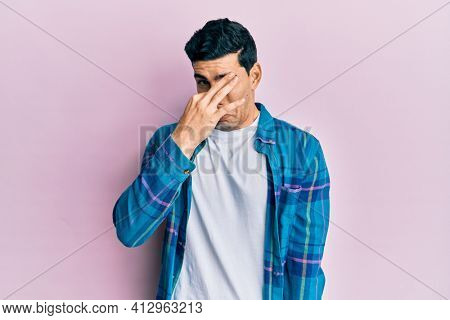 Handsome hispanic man wearing casual clothes smelling something stinky and disgusting, intolerable smell, holding breath with fingers on nose. bad smell