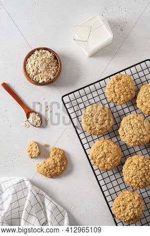 Delicious And Crunchy Oatmeal Cookies, Oatmeal Flakes And A Cup Of Milk On White Background. Recipe,