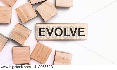 On A Light Background, Wooden Cubes And A Wooden Block With The Text Evolve. View From Above