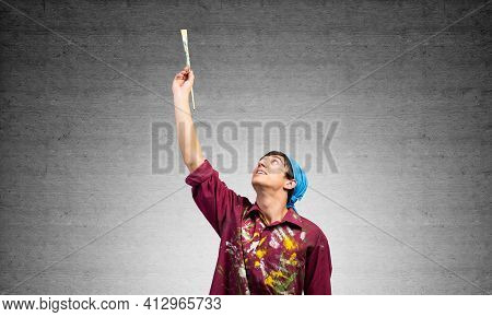 Young Painter Artist Pointing Upwards. Man Holds Paintbrush Over His Head. Portrait Of Caucasian Pai