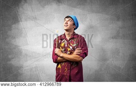 Smiling Young Painter Artist With Folded Arms. Portrait Of Happy Decorator Looking Upwards On Gray W