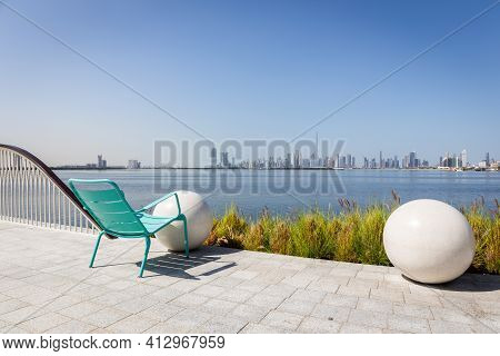 Dubai, Uae, 22.02.2021. Green Chair On A Promenade Overlooking Dubai Downtown With Burj Khalifa Buil