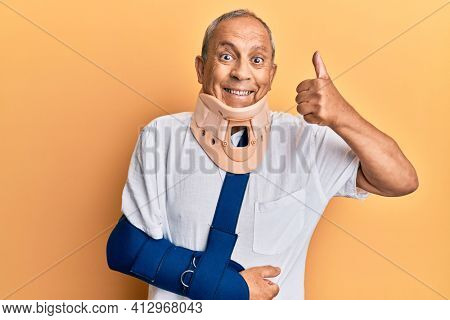 Handsome mature senior man wearing cervical collar and arm on sling approving doing positive gesture with hand, thumbs up smiling and happy for success. winner gesture.