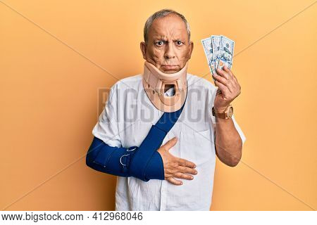 Handsome mature injured man wearing cervical collar and sling holding insurance money skeptic and nervous, frowning upset because of problem. negative person.