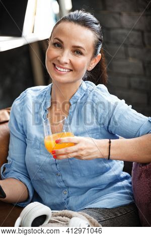 Leisure time concept. Happy beautiful woman talks on a phone and drinks orange juice from glass sitting on a couch indoors. Female spending her free day and relaxing at home alone.