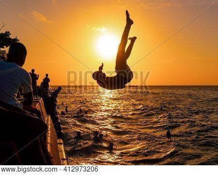 Stone Town, Zanzibar, Tanzania - January 2020: Locals Run And Jump Into The Sea From Stone Embarkmen