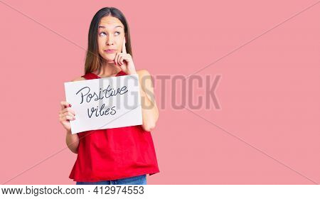 Beautiful brunette young woman holding positive vibes banner serious face thinking about question with hand on chin, thoughtful about confusing idea