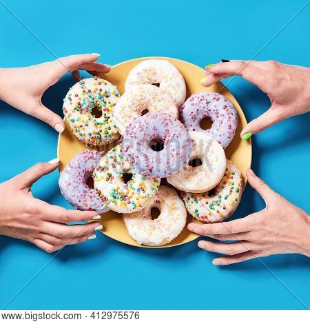 Celebrating National Donut Day. Different Colourful Round Glazed Donuts With Sprinkles On Plate Over