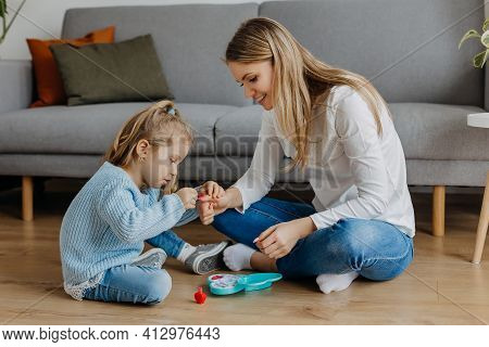 Mother And Little Daughter Paint Their Nails With Toy Nail Polish