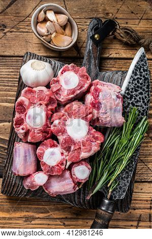 Raw Beef Oxtail Cut Meat On Wooden Cutting Board With Knife. Wooden Background. Top View
