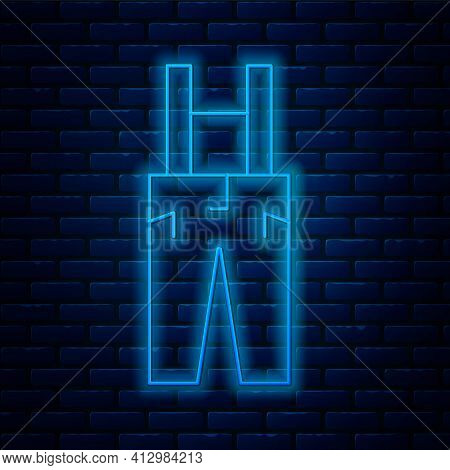 Glowing Neon Line Pants With Suspenders Icon Isolated On Brick Wall Background. Vector