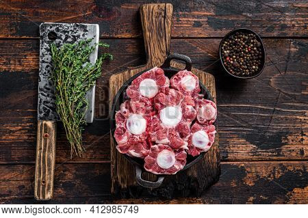 Raw Veal Beef Oxtail Meat On Butcher Wooden Board With Cleaver. Dark Wooden Background. Top View