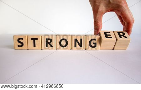 Strong Or Stronger Symbol. Businessman Turns Wooden Cubes, Changes The Word 'strong' To 'stronger'.