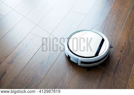 Photo Of A White Robot Vacuum Cleaner Working On The Floor In The House. Cleaning