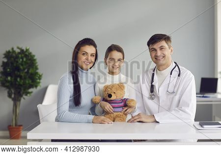 Portrait Of Happy Mother, Daughter And Their Family Practitioner Smiling At Camera