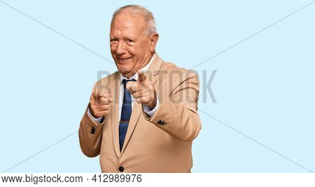Senior caucasian man wearing business suit and tie pointing fingers to camera with happy and funny face. good energy and vibes.