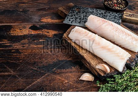 Raw Cod Loin Fillet Steak On Wooden Board With Butcher Cleaver. Dark Wooden Background. Top View. Co