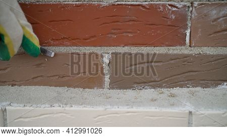 Worker Wipes The Seams Outside The Brick House. Construction Mason Worker Bricklayer Installing Red
