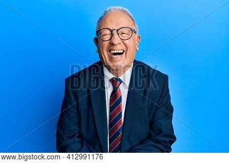 Senior caucasian man wearing business suit and tie smiling and laughing hard out loud because funny crazy joke with hands on body.