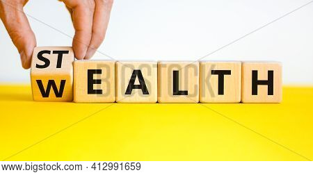 Stealth Wealth Symbol. Businessman Turns The Wooden Cube And Changes The Word 'wealth' To 'stealth'.