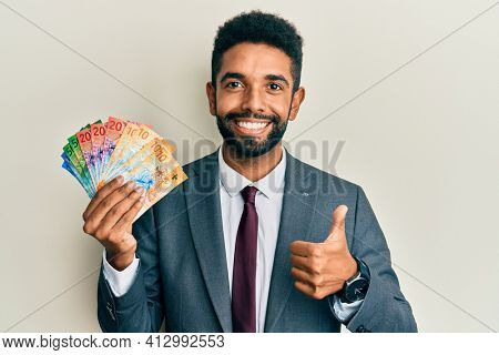 Handsome hispanic business man with beard holding swiss franc banknotes smiling happy and positive, thumb up doing excellent and approval sign