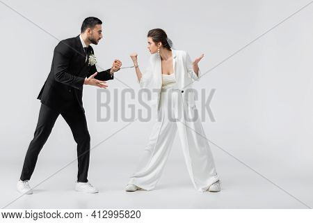 Aggressive Interracial Bride And Groom In Handcuffs Looing At Each Other On White Background.