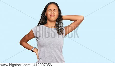 Young african american girl wearing casual clothes suffering of neck ache injury, touching neck with hand, muscular pain