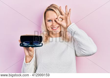 Beautiful caucasian blonde woman holding glasses in eyewear case smiling happy doing ok sign with hand on eye looking through fingers