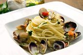 dish of spaghetti with clams on wooden table poster