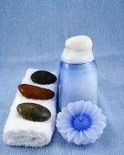 a spa still life on a blue background consisting of a bottle of lotion, a candle, a towel and some stones poster