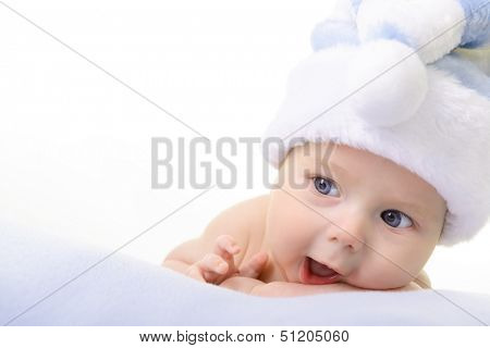 christmas cute baby boy lying on blue soft plaid like on snowdrift, beautiful infant in Santa's hat