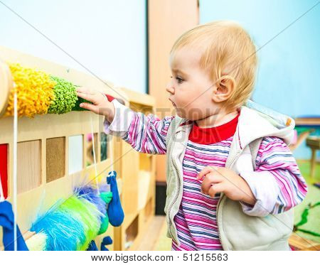 cute little boy in the classroom early development plays with  bright toys
