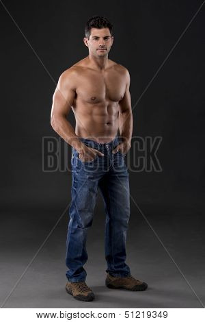 Portrait of a strong man posing without a shirt against dark background
