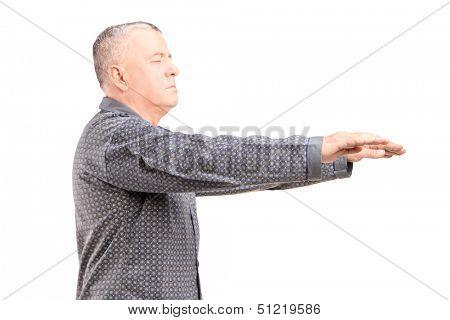 Mature man in pajamas sleepwalking isolated on white background