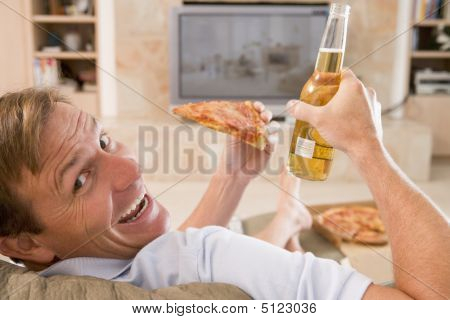 Man Enjoying Beer And Pizza In Front Of Tv