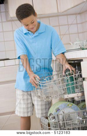 Young Boy Loading Dishwasher