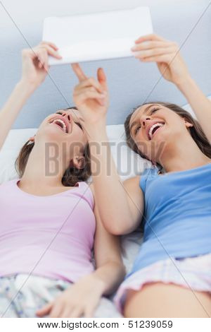 Girls lying in bed holding tablet and pointing to it at sleepover