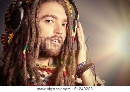 Portrait of a happy rastafarian young man listening to music in headphones. poster
