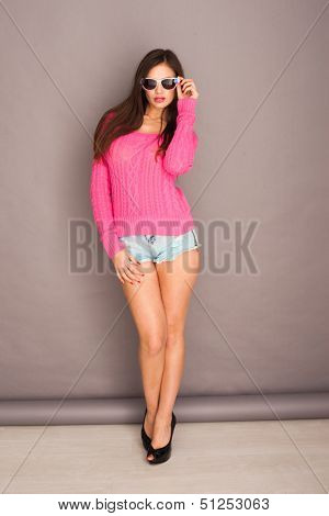Beautiful sexy young woman with long brunette haie wearing sunglasses in skimpy shorts and high heels posing against a grey wall showing off her long shapely legs